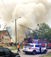 Detroit firefighters work an explosion at a home on Detroit's east side Tuesday, Aug. 6, 2019. Fire officials in Detroit are investigating the cause of the explosion that collapsed a home Tuesday afternoon and an ensuing fire scorched at least one neighboring house. No injuries were reported.
