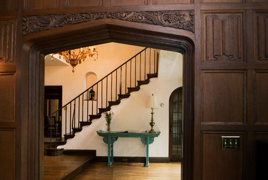 The carved wood panelling entrance in the living room frames the foyer and iron staircase.