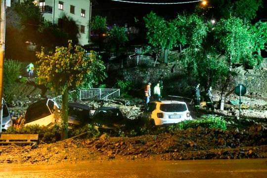 Rescuers stand next to capsized car after they were hit by a landslide in Casargo, near the northern Italian town of Lecco, in the early hours of Wednesday, Aug. 7, 2019.