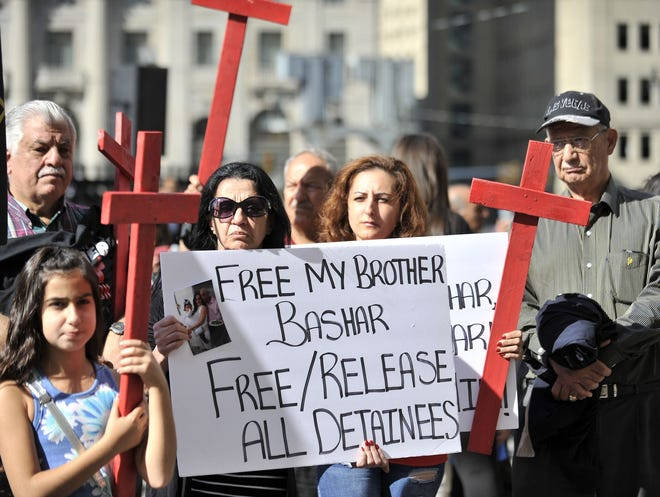 Ghada Babbie of Farmington Hills, wearing sunglasses, and her sister-in-law, Sonya Babbie, of Warren demonstrate for relative Bashar Babbie at a rally outside federal court Thursday in Detroit in support of Iraqis detained by Immigration and Customs Enforcement.