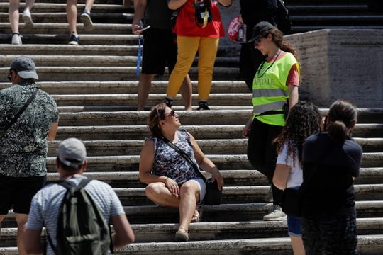 A Police officer asks a woman not to sit on the Spanish Steps, in Rome, Wednesday, Aug. 7, 2019. Police started the enforcement of a law designed to protect monuments and landmarks and are forbidding people from sitting on the Spanish steps since they are considered a monument.