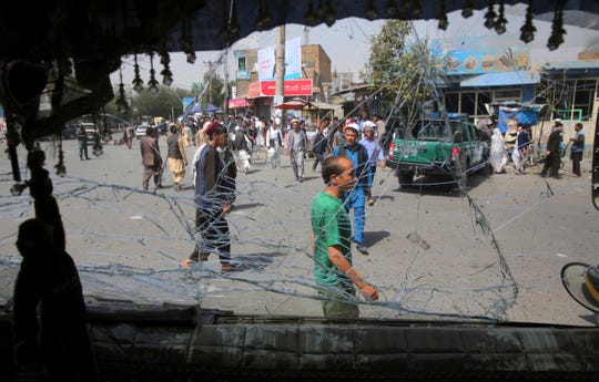 Afghans are seen through a shattered glass of a transport bus broken after an explosion in Kabul, Afghanistan, Wednesday, Aug. 7, 2019. A suicide car bomber targeted the police headquarters in a minority Shiite neighborhood in western Kabul on Wednesday, setting off a huge explosion that wounded dozens of people, Afghan officials said. The Taliban claimed responsibility for the bombing.