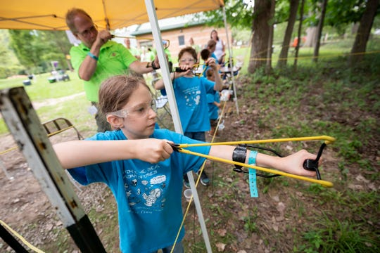 Eight-year-old Violet Osantowske of St. Clair Shores practices using a slingshot during a Cub Scouts STEM camp at Stage Nature Center in Troy.
