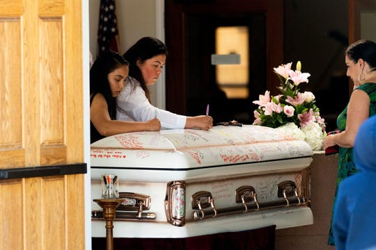 Mourners write on Keyla Salazar's casket during the 13-year-old's funeral on Tuesday, Aug. 6, 2019, in San Jose, Calif.