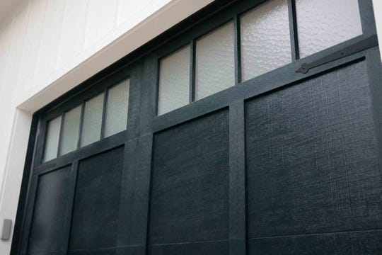"AT HOME for release MARCH 2019 HOME TOUCH Caption 05: Haas Door's carriage-house style garage doors are painted in ""cool black"" with a wood texture and feature specialty glazed glass windows. Insulated steel garage doors are energy-efficient, low-maintenance and won't crack, warp or split when installed properly. Hinge-straps and door pulls can be the finishing touches that elevate a garage door from a standard to stellar design."