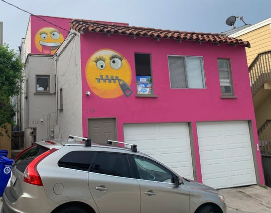 Painted emoji are seen on a house in Manhattan Beach, Calif. on Wednesday, Aug. 7, 2019. The Southern California seaside community is in an uproar after the home was given the new paint job featuring two huge emojis on a bright pink background. Manhattan Beach residents railed against the makeover during a City Council meeting Tuesday night, citing problems with spectators.