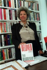 "In this Sept. 1987 file photo, author Toni Morrison poses with a copy of her book ""Beloved"" in New York."