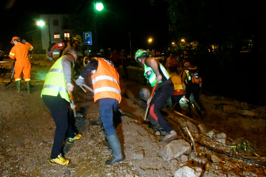 Rescuers work to clear mud from the roads of Casargo. Italian firefighters say 200 people have been evacuated following a Tuesday landslide in a mountainous area in the northern Lombardy region.