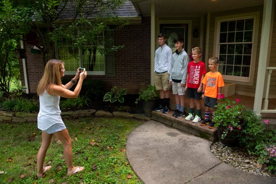 Rachel Arrington makes the annual first day of school portrait of her four sons, from left, Nate, 13, Wes, 11, Eli, 9, and Ty, 7, in front of their Evansville home Wednesday morning.