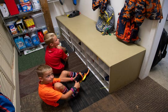 Ty Arrington, 7, left, and Eli, 9, put on their shoes and prepare to head out the door with their mom, Rachel, for their first day of school Wednesday morning.