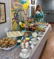 Debbie Newman from Portage Retail Center displays fine china it donated for the Catawba Island Garden Club tea party at Union Chapel Museum