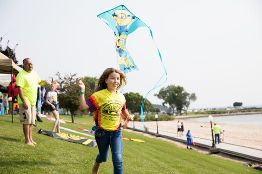Kendra Feld runs to get a kite airborne at a past Soar on the Shore kite festival in Algoma.