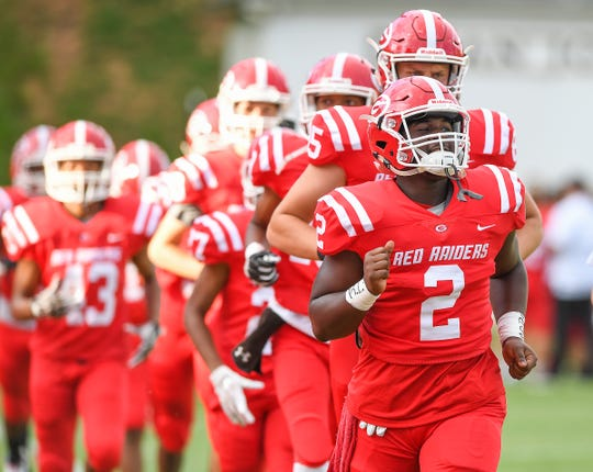 GreenvilleÕs Trey Scott (2) leads a portion of the Red Raiders onto the field during pregame before their game against Woodmont Friday, August 17, 2018 at Sirrine Stadium in Greenville.