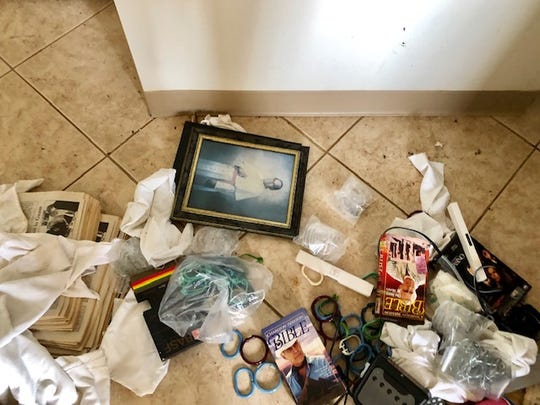 Some trash and discarded items, including a glass-framed photograph of disgraced former Guam Archbishop Anthony Apuron, on the floor of one of the fourth-floor rooms of the former Accion Hotel and former Redemptoris Mater Seminary in Yona.