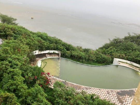 A view of the ocean and the pool with green stagnant water, from one of the fourth-floor rooms of the former Accion Hotel during the rainy morning hours of Aug. 7, 2019.