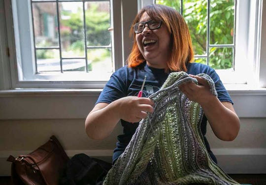Tiffianni Rusadi laughs while working on her project during a Drunken Knitwit meeting in Indianapolis on July 28, 2019.