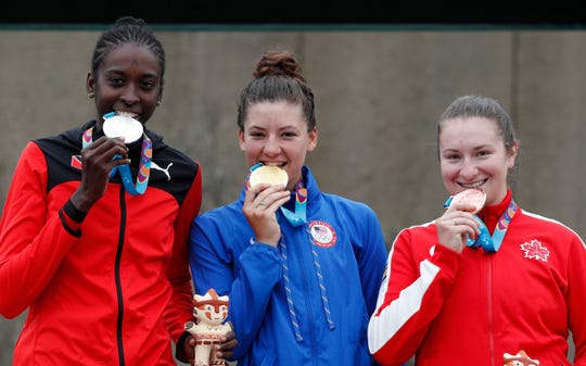 Silver medalist Teniel Campbell of Trinidad and Tobago, from left, gold medalist Chloe Dygert of the United States, and bronze medalist Laurie Jussaume of Canada, pose for photos during the medal ceremony for the women's road cycling individual time trial finals at the Pan American Games in Lima Peru, Wednesday, Aug. 7, 2019.