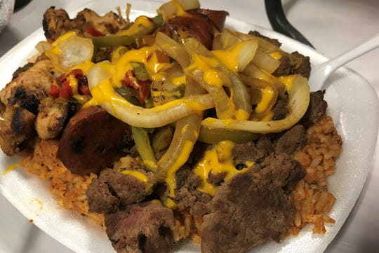 Blackened chicken, andouille sausage, grilled steak, sauteed onions and bell peppers and cheese sauce top jambalaya rice for the Cajun Queen. It's on the list of the best Indiana State Fair 2019 foods.