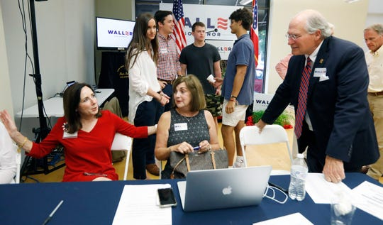 Former Mississippi Supreme Court Chief Justice Bill Waller Jr., a Republican gubernatorial candidate, right, and his wife, Charlotte Waller, left, speak with supporters at Waller's headquarters in Jackson, Miss., Tuesday, Aug. 6, 2019, after polls closed. (AP Photo/Rogelio V. Solis)