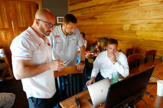 Mississippi Gubernatorial candidate Robert Foster, right, checks in with his media consultant Jordan Brumbelow, left, and campaign manager Colton Robison as they await election results at Uncle Bubba's BBQ in Hernando, Miss. on Tuesday, Aug. 6, 2019.
