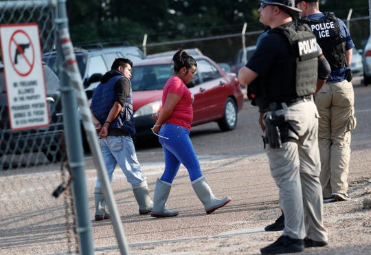 Two people are taken into custody at a Koch Foods Inc. plant in Morton, Miss., on Wednesday, Aug. 7, 2019.  U.S. immigration officials raided several Mississippi food processing plants on Wednesday and signaled that the early-morning strikes were part of a large-scale operation targeting owners as well as employees.