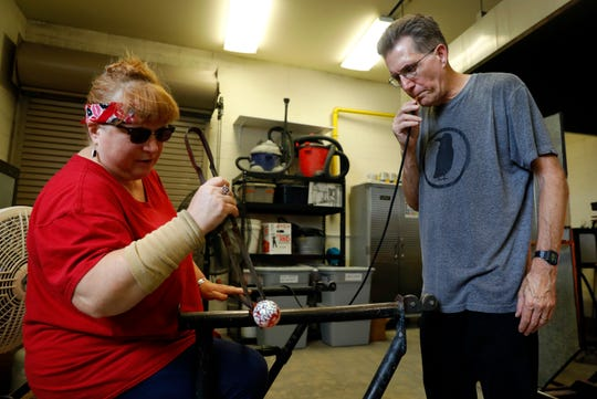 Theresa Sharp, left, studio manager for the Ohio Glass Museum shapes an ornament as Eagle-Gazette reporter Jeff Barron blows air into a tube to shape the glass into a ball Wednesday, Aug. 7, 2019, in downtown Lancaster.