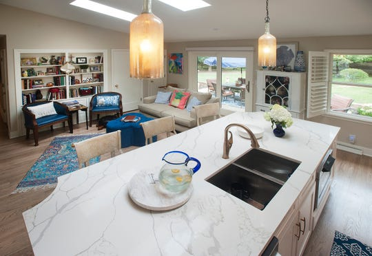 The open-concept kitchen island overlooks the hearth room in the Arnold home.29 July 2019