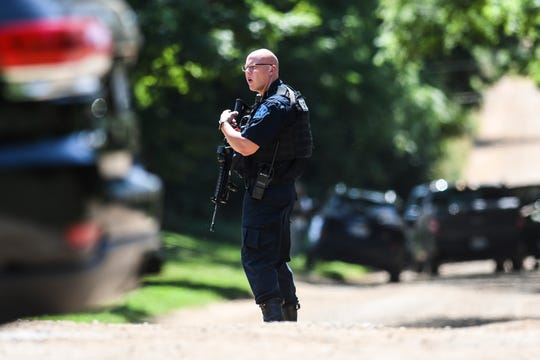 A member of the Michigan State Police and other agencies search for a man near the corner of Smith and Bunker Roads in Eaton Rapids, Wednesday, Aug. 7, 2019.