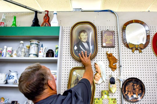 Ken Stone places the copy of a portrait of his grandfather he recently found at The Mega Mall antiques and collectibles market while getting more information about where the photo came from on Tuesday, Aug. 6, 2019, in DeWitt Township.