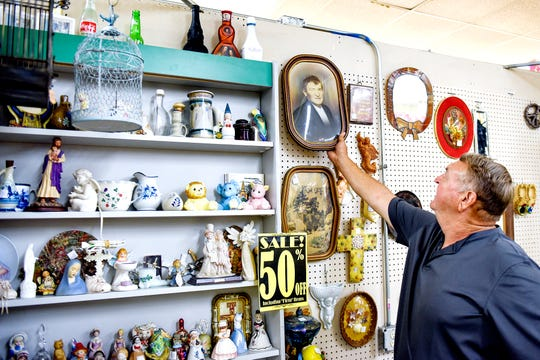 Ken Stone takes down the copy of a portrait of his grandfather he recently found at The Mega Mall antiques and collectibles market while getting more information about where the photo came from on Tuesday, Aug. 6, 2019, in DeWitt Township.
