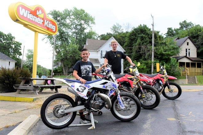 Lakoda Leedy, left, 10, and Ian Wolfe, 17, stand by the motorcycles they will race Friday night at the Richland County Fair.