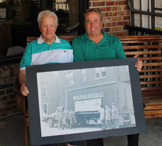 Servex Electronics founder Charlie Sens, left, and his son Greg Sens display a photograph of a truckload of television tubes being delivered to the company early in its history.