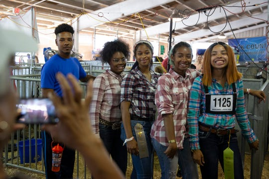 From left, Brandon Albright, 18; Raynhia Robinson, 16; Kristine Blackwell, 17; Tia Belle-Anderson, 17; and Arianna Taylor, 17, of Vincent High School pose for a photo taken by Arianna's grandmother, Helen Harris, following the Market Lamb Show at the Wisconsin State Fair on Wednesday.