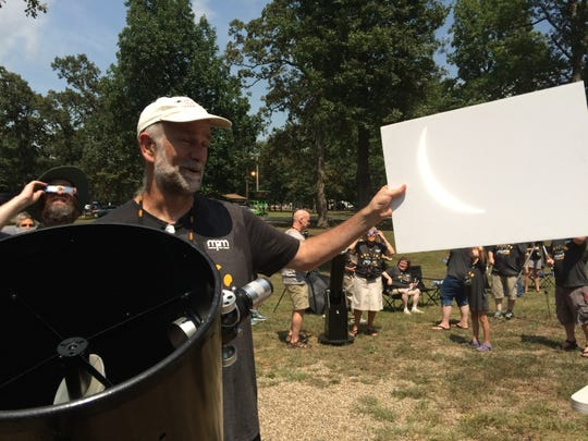 Bob Bonadurer, director of the Milwaukee Public Museum's Daniel M. Soref National Geographic Dome Theater & Planetarium, shows a sliver of the moon during a total solar eclipse in 2017 in Metropolis, Illinois.