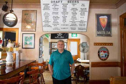 Mike Romans hand writes the beer menu for his craft beer bar Romans' Pub.