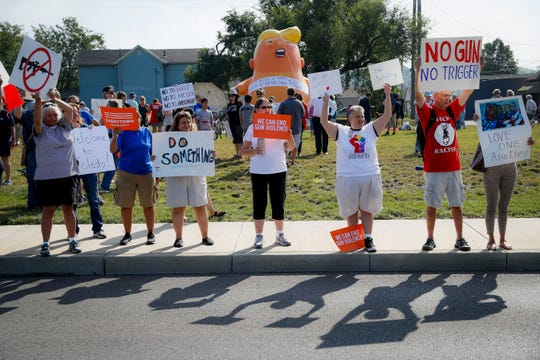 People gather to protest the arrival of President Donald Trump outside Miami Valley Hospital after a mass shooting that occurred in the Oregon District early Sunday morning, Wednesday, Aug. 7, 2019, in Dayton, Ohio. (AP Photo/John Minchillo)