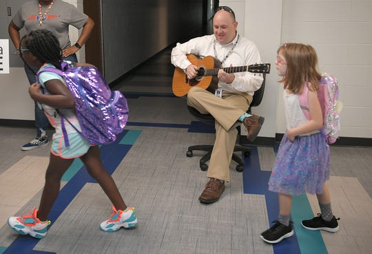 Franklin Elementary School music teacher Patrick Bourn plays music as students enter the school on the first day of school in Franklin on Wednesday, August 7, 2019.