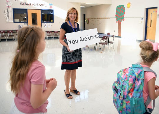 Franklin Elementary School teachers welcome back students with signs of kindness on the first day of school on Wednesday, August 7, 2019.