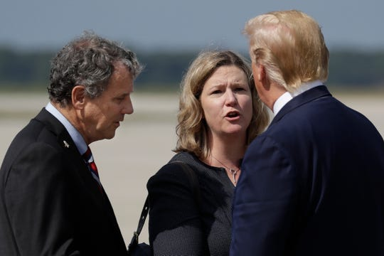 President Donald Trump is greeted by Dayton Mayor Nan Whaley and Sen. Sherrod Brown, D-Ohio, after arriving at Wright-Patterson Air Force Base to meet with people affected by the mass shooting in Dayton, Wednesday, Aug. 7, 2019, in Wright-Patterson Air Force Base, Ohio. (AP Photo/Evan Vucci)