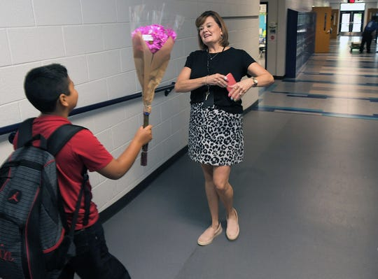 Franklin Elementary School student Edin Lopez, 8,. greets his third grade teacher, Tammy Lovell, with flowers on the first day of school in Franklin on Wednesday, August 7, 2019.
