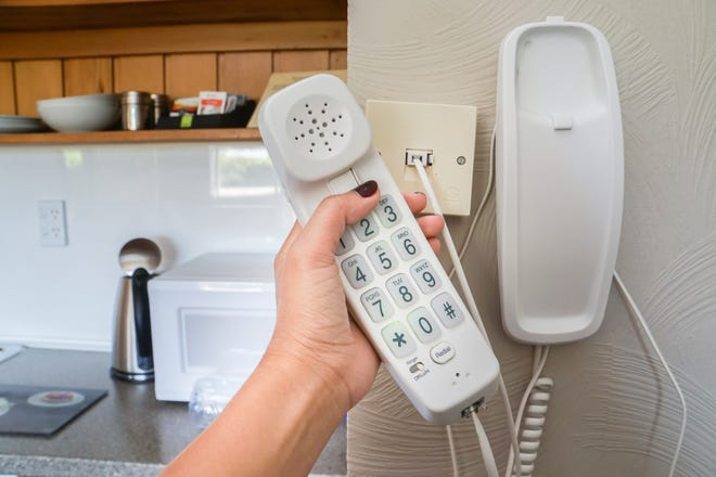 Woman holds a landline telephone.
