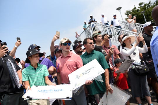 Fans watch as Tiger Woods walks into a press conference after finishing his practice round of the Northern Trust Open at Liberty National Golf Course on Wednesday, August 7, 2019, in Jersey City.
