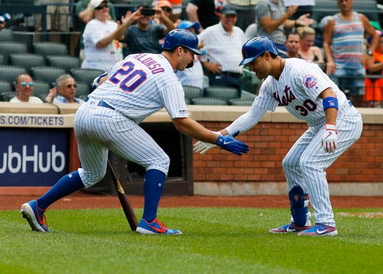 New York Mets right fielder Michael Conforto (30) celebrate with first baseman Pete Alonso (20) after hitting a solo home run against the Miami Marlins during the seventh inning at Citi Field.