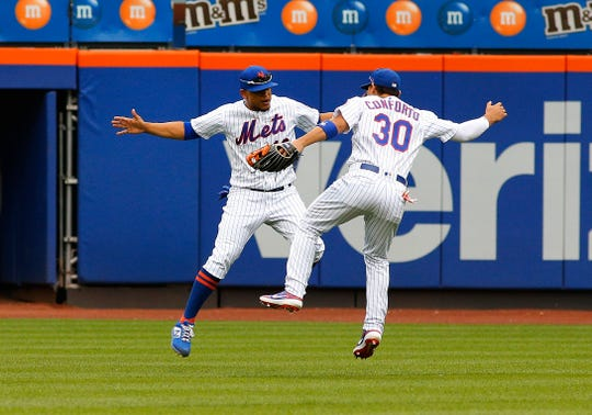 New York Mets right fielder Michael Conforto (30) and center fielder Juan Lagares (12) react after defeating the Miami Marlins at Citi Field.