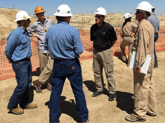 Chevron personnel and state oil regulators , including Inland District Deputy Cameron Campbell (in orange hard hat) and Acting Oil and Gas Supervisor Jason Marshall discuss the massive Cymric blowout in Kern County on July 19, 2019.