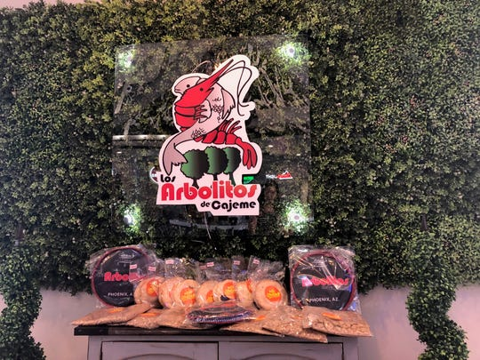A table displaying Los Arbolitos de Cajeme merchandise stands under a sign inside the restaurant in Phoenix. This is the chain's first U.S. location.