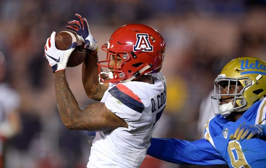 Arizona wide receiver Devaughn Cooper, left, makes a catch as UCLA defensive back Elijah Gates defends during the second half of an NCAA college football game Saturday, Oct. 20, 2018, in Pasadena, Calif.