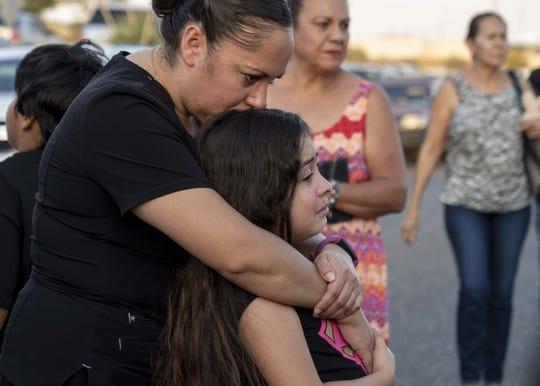 Myra Diaz, 34, consoles her daughter Liana Rubio, 7, outside Walmart in El Paso, Texas, on Aug. 6, 2019.