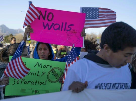 Gente protesta contra el muro fronterizo de Trump.