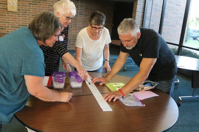 Local poll workers check the results after voters in the Benton-Carroll-Salem Local School District again rejected another emergency tax levy in a special election on Tuesday.